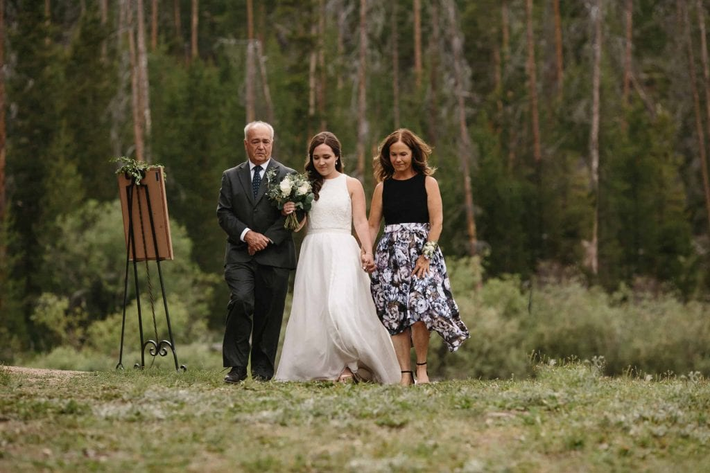 bride walks down aisle with parents before wedding ceremony