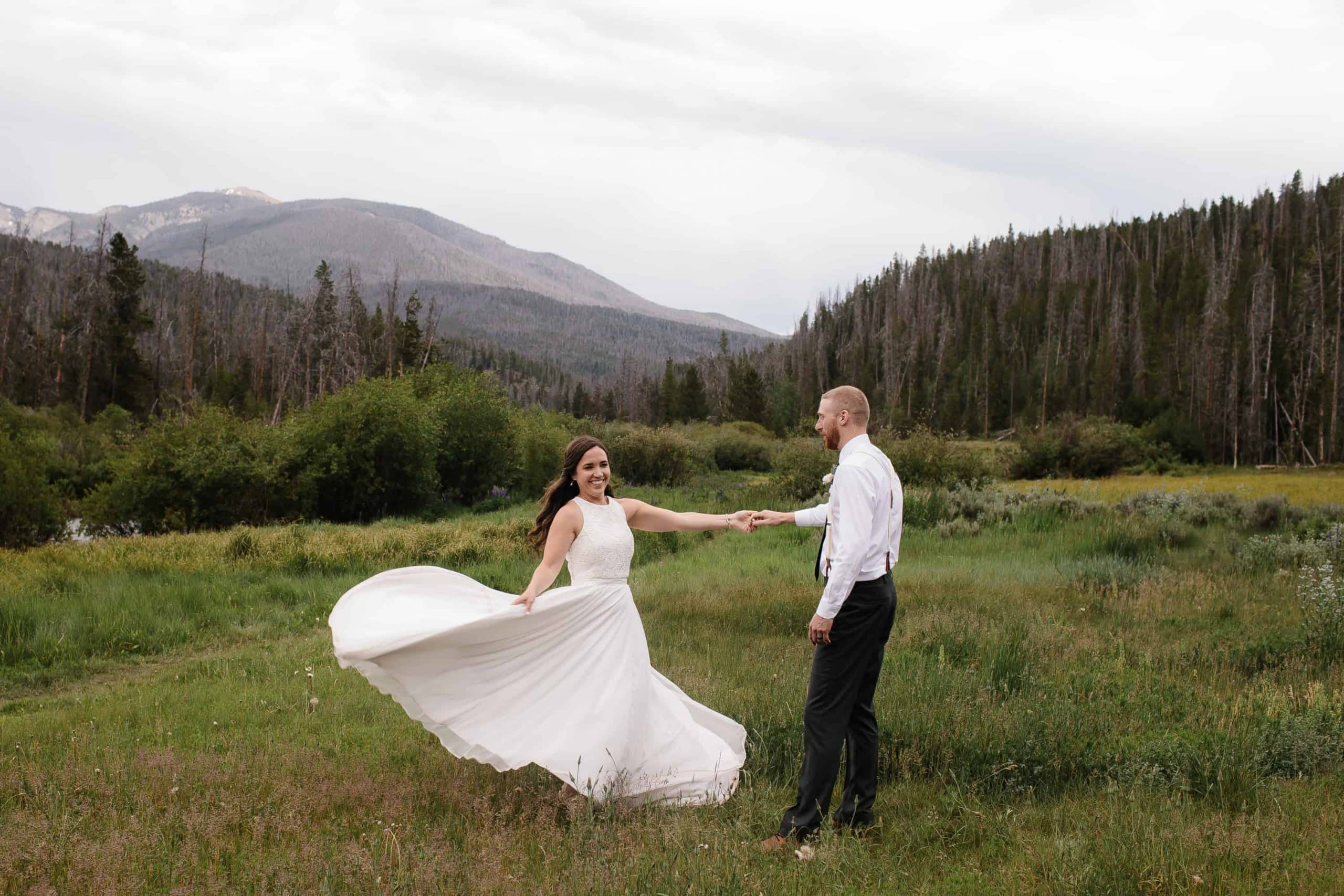 bride and groom dance in a fields after ceremony