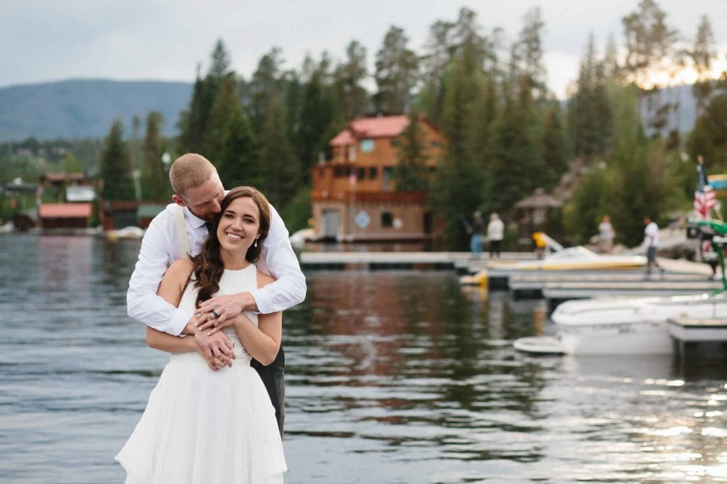 bride and group hug on a dock in Grand Lake CO