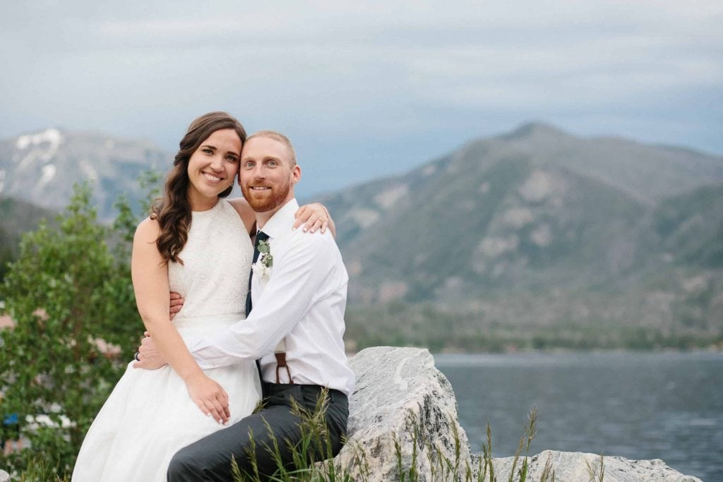 bride and groom sit together at Grand Lake