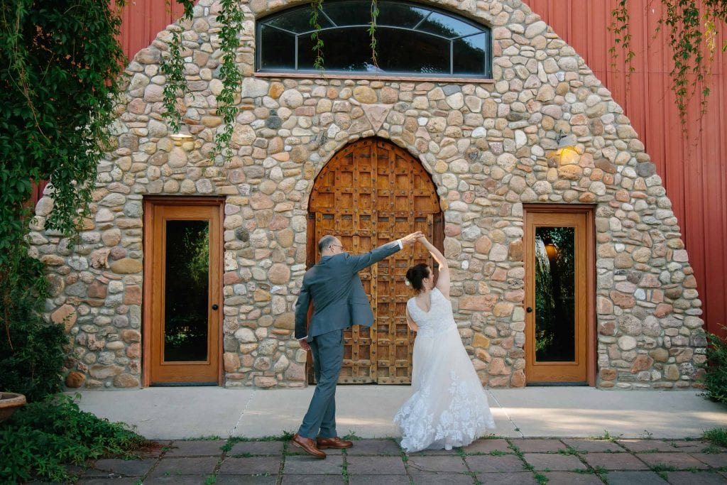 groom spins his bride outside of reception