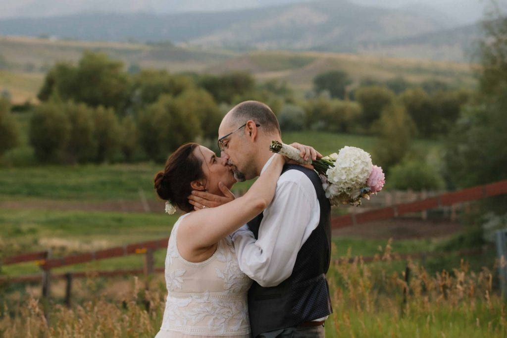 a kiss between bride and groom at sunset
