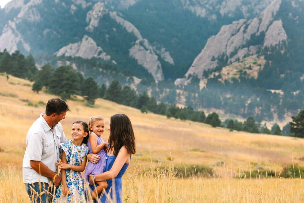 family snuggles against a view of the flatirons