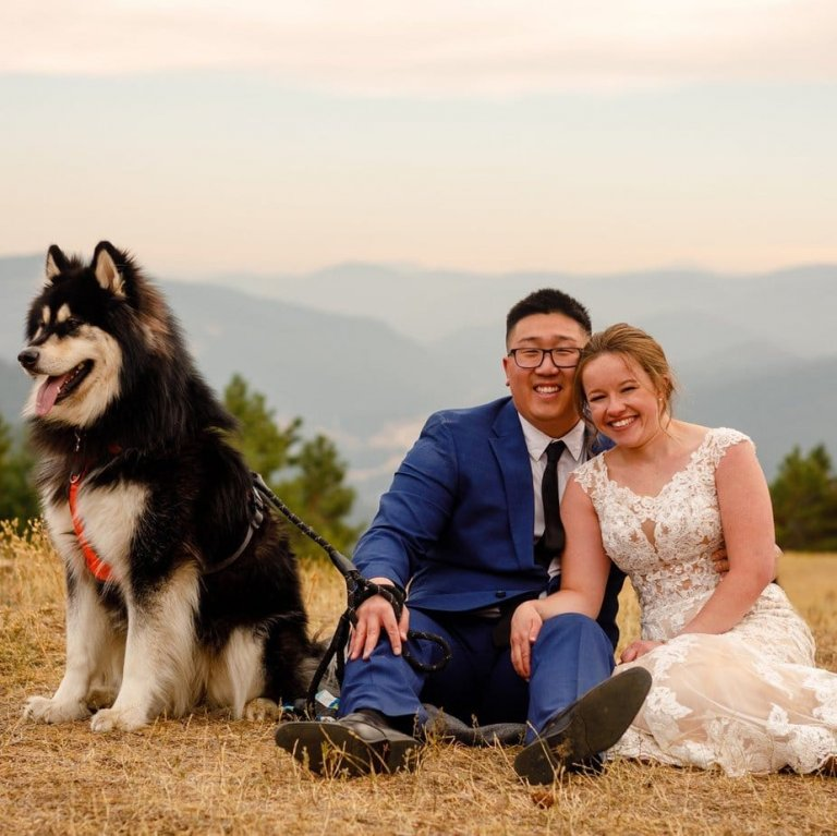 A bride and groom snuggle together with their dog after eloping with their dog.