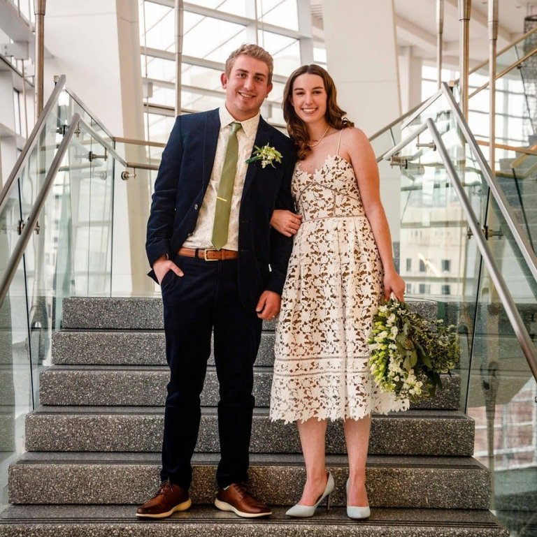A bride and groom pose for the camera after eloping in a courthouse in Denver.
