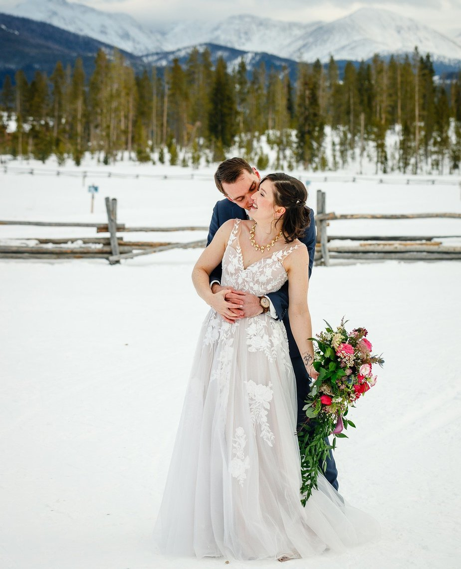a couple elopes in the snow at devil's thumb ranch
