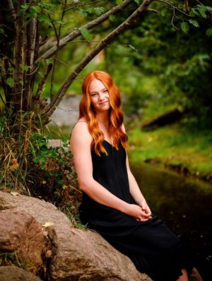 senior photo by a river in boulder on a rock