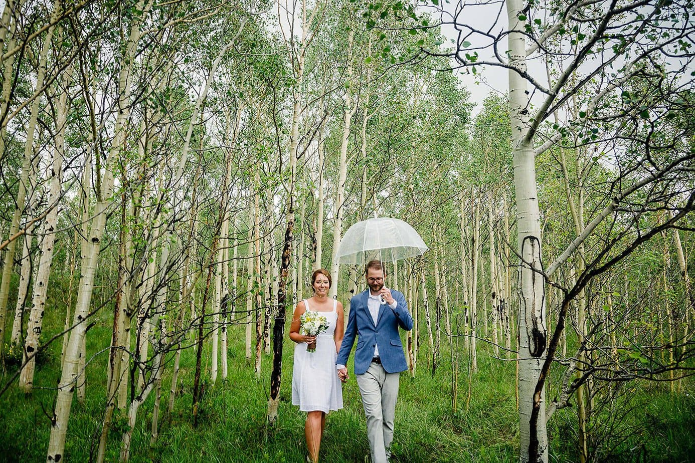 a couple holds hands through the aspen trees after their elopement